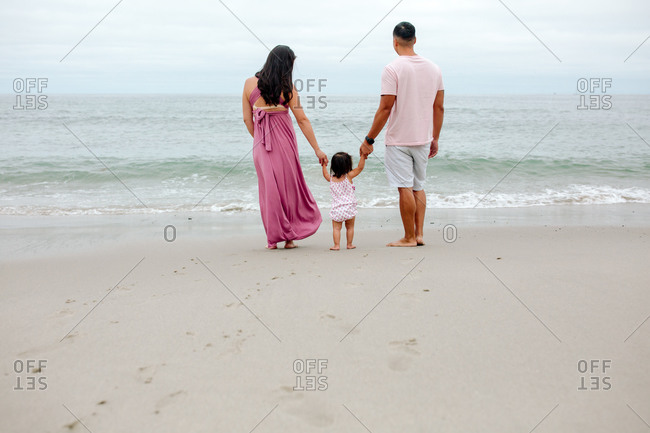 Young parents with small child between them on beach gazing at ocean