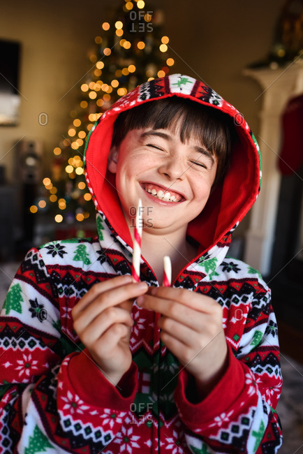 Happy boy in festive pajamas eating a candy cane at Christmas time.
