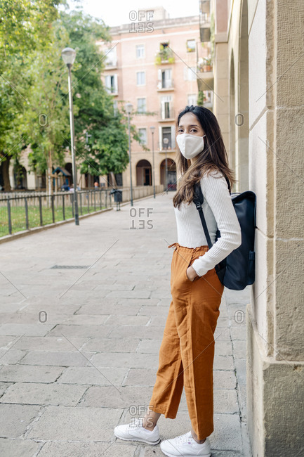 Side portrait woman wearing mask and backpack by portal in old city