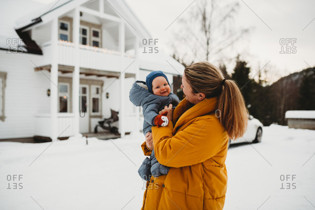 Mom and adorable baby smiling on cold snowy day outside white house