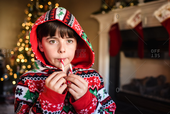 Cute boy in festive pajamas eating a candy cane at Christmas time.