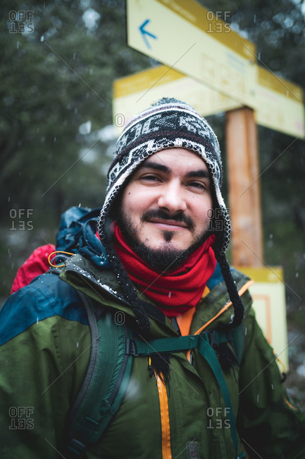 Man smiling to camera with cold protection next to a trekking sign
