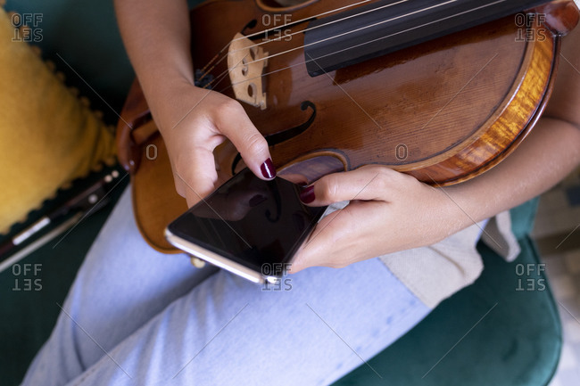 Young girl's hands chat with the cell phone while holding a viola.