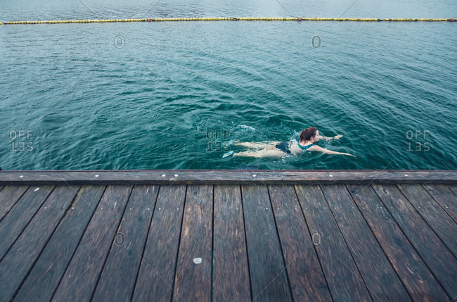 Woman Swimming Solo Next to Wooden Dock in Cold Water in Denmark