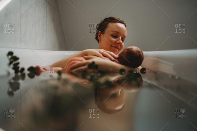 Reflection on water of happy mum nursing newborn baby in bath tub