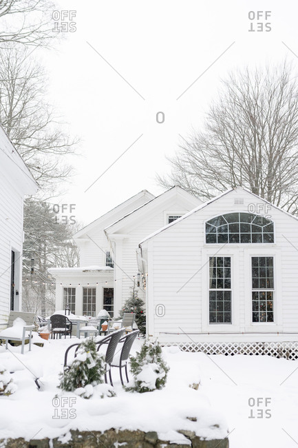 White house with patio in the snow with lights and Christmas tree