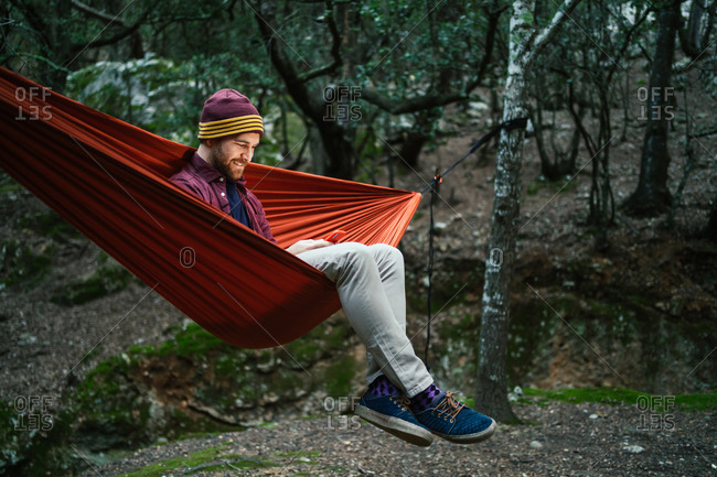 Young male uses his smartphone resting on a hammock in the woods
