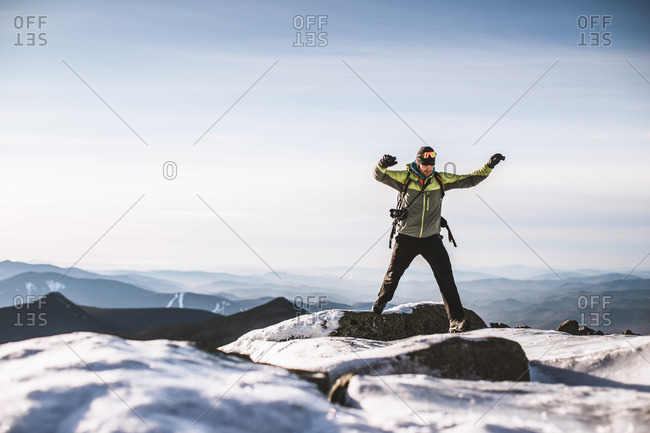 Man with camera jumps from icy rock on mountain summit in winter