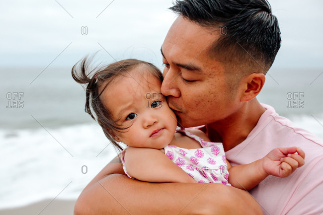 Loving Asian dad cradles young daughter in his arms at the ocean
