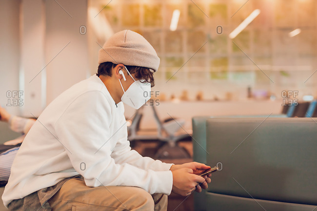 Pre-teen boy wearing a mask using phone to kill time at airport.
