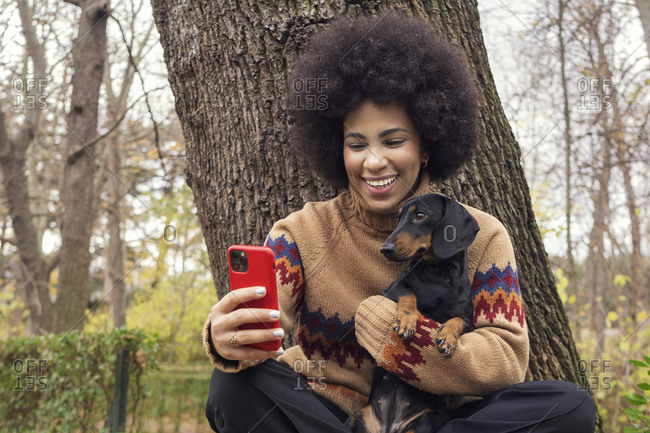 a Cuban girl taking a selfie with her dachshund in the park
