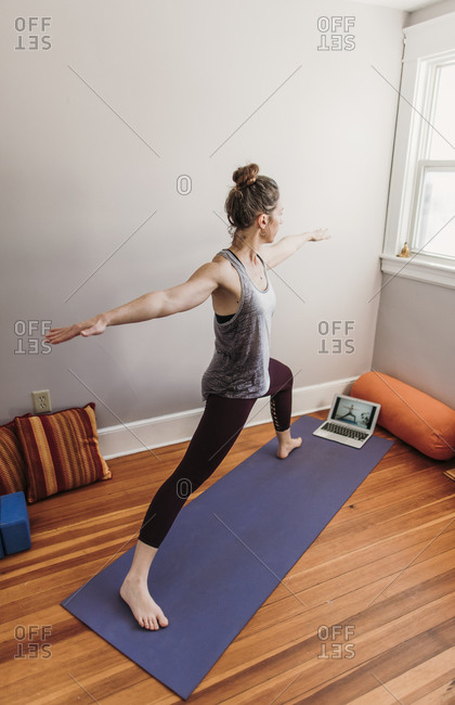 fit woman in her home practices yoga in front of a computer