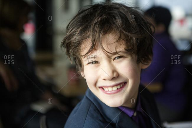 Portrait of a happy boy in a suit sitting in window light