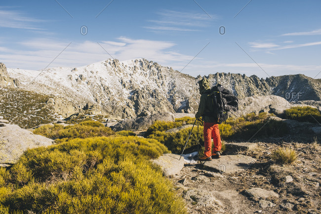 Young man looking at his objective summit during hike stop, Gredos, Avila, Spain