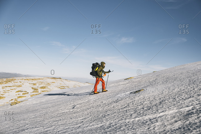 Young male hiking uphill on snow against clear blue sky, Gredos, Avila, Spain