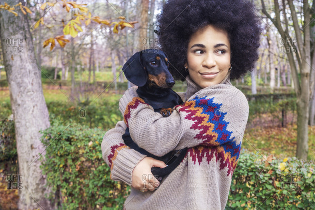 African American girl sitting and hugging her dog in the park in autumn