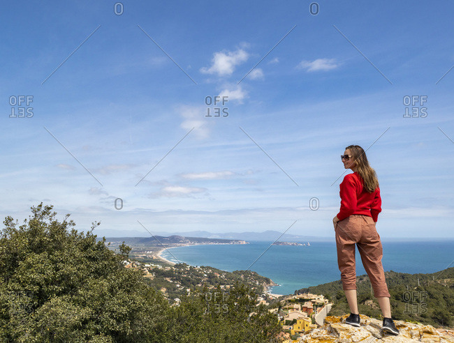 Cheerful girl dressed in red enjoying the coast and looking at the sea