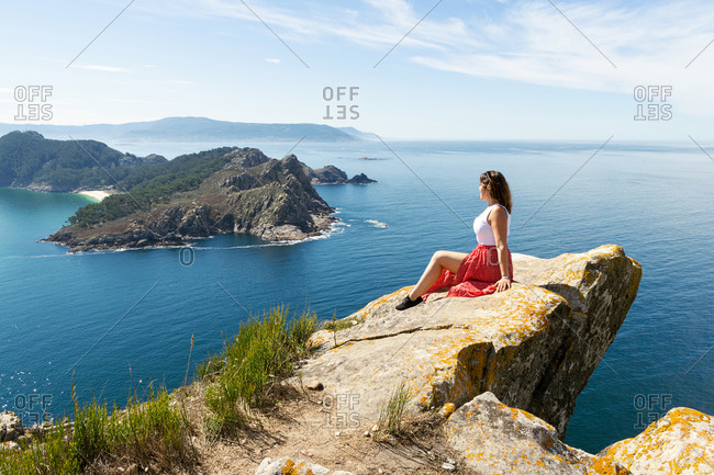 Young woman sitting on a cliff with the Cies Islands in the background