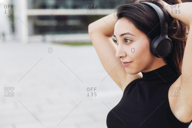 Close up portrait of a young girl in head phones looking into distance