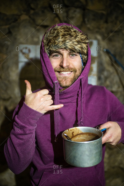 Man with a hoodie looks at camera smiling and making gesture with hand