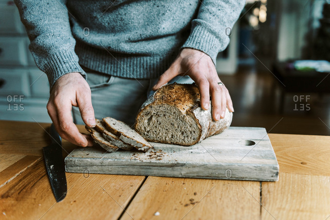 Hands of a man holding and cutting a rustic sourdough bread with knife