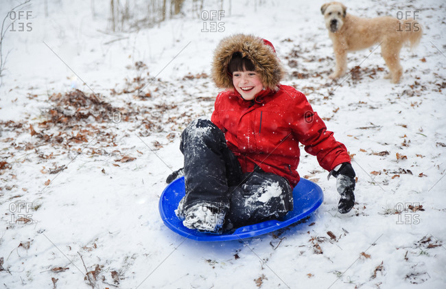 Happy boy sledding down a hill on snowy winter day while dog watches.
