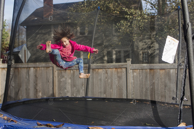 A joyful little girl with wild hair jumps on trampoline with mesh net