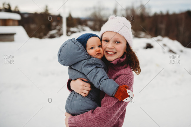Smiley Big sister holding baby brother outside in the snow on cold da