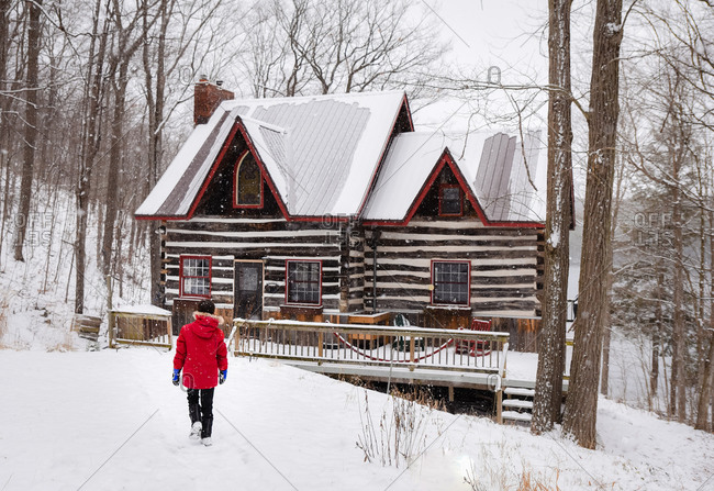 Boy in red winter coat walking towards log cabin on snowy winter day.