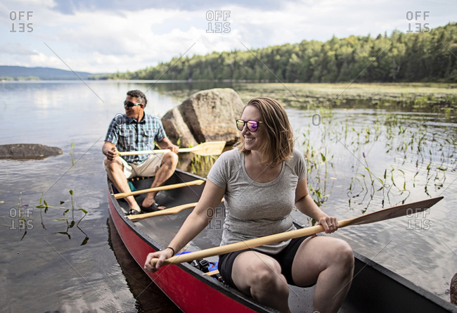 Smiling mid adult couple paddle in red canoe among lily pads on lake