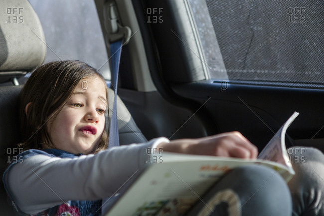 A cute little girl sits in a car seat in sunlight studying a book