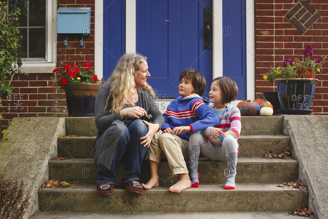 A smiling Mom sits with her two children on front stoop of home
