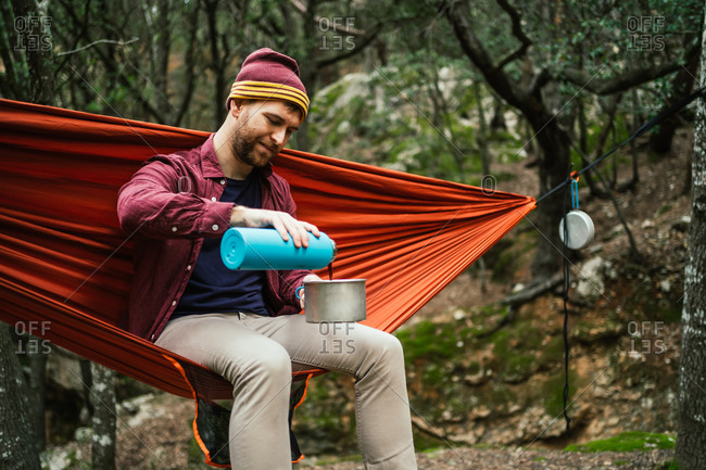 Man pours hot beverage on a pot sitting on a hammock in forest