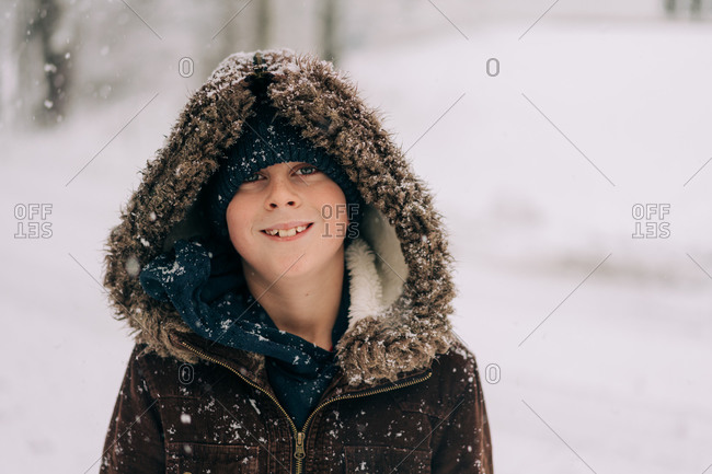 boy wearing a fluffy hood smiling at the camera on a snow day