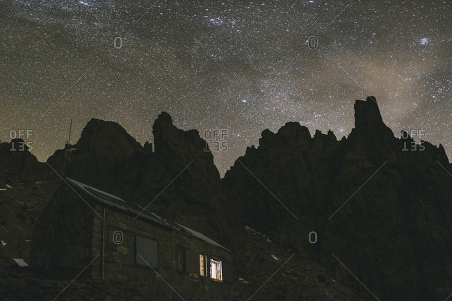 Galayos refuge against granite spikes and Milky Way during a winter night, Gredos, Spain