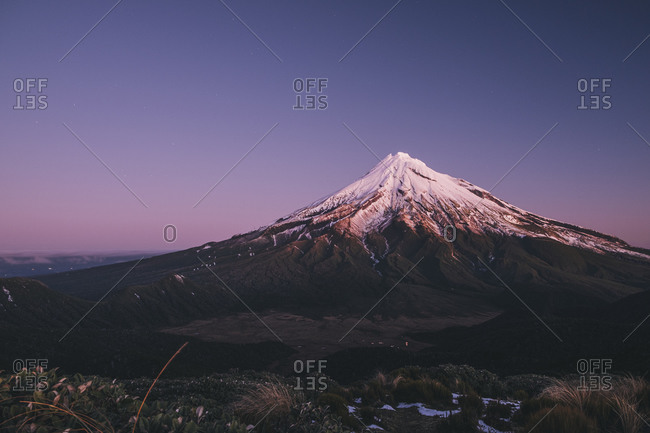 Mount Taranaki volcano after the first snowfall of the season at sunset, New Zealand.