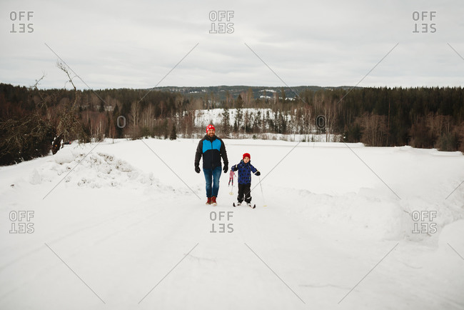 Father and son walking up a slope with skis in snowy winter day Norway