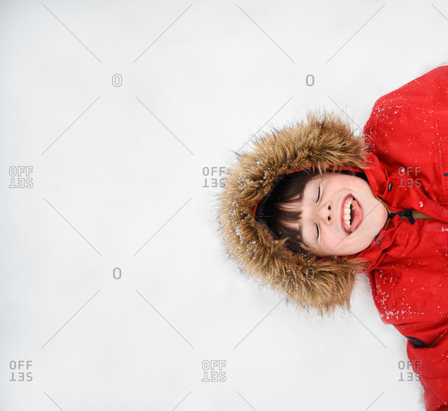 Overhead of happy boy in red coat with furry hood laying in the snow.