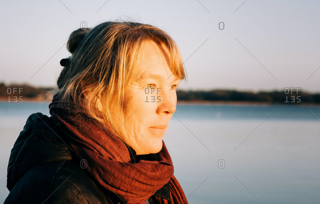 close up portrait of a Swedish lady looking out to the sea at sunset