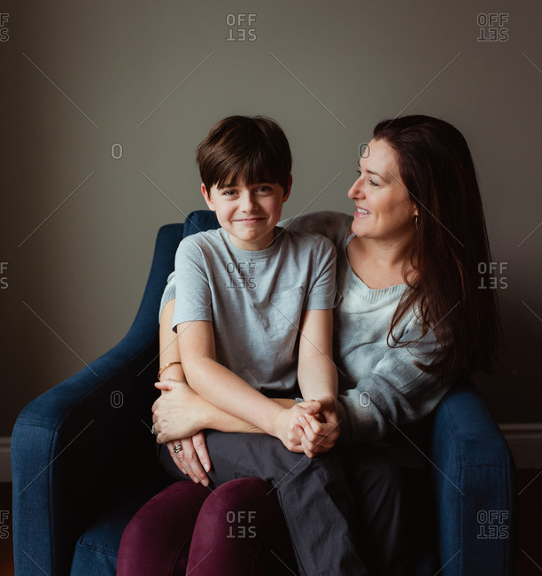 Happy woman hugging her son as he sits in her lap on a chair.