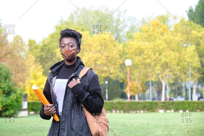 University female african student wearing protective face mask outside on campus. New normal in college.