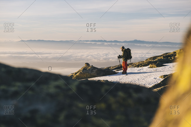 Young man wearing cap and looking at sun rising above horizon, against clouds, Gredos, Spain