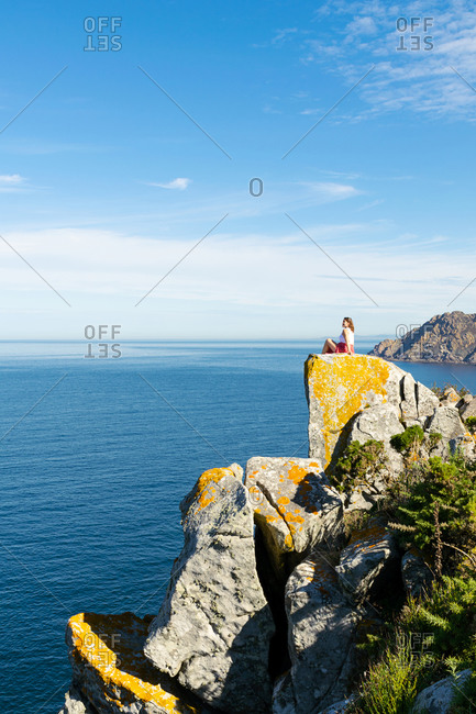 Woman sitting on the edge of a rocky cliff in the Cies Islands - Galicia