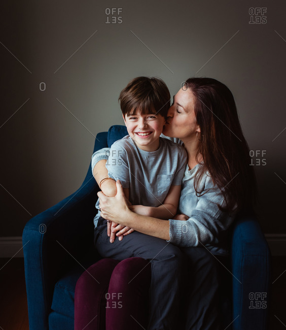 Woman hugging and kissing her son as he sits in her lap on a chair.