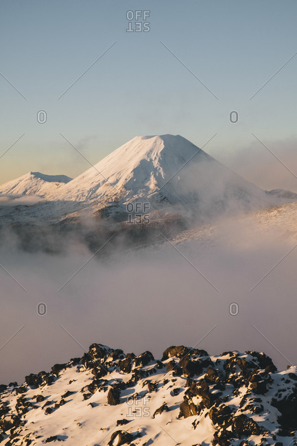 Mt Ngauruhoe stratovolcano rising above the mist down the valley at Tongariro National Park, New Zealand
