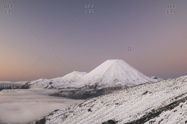 Mt Ngauruhoe above the mist tinted in pastel purple colors during winter at Tongariro National Park