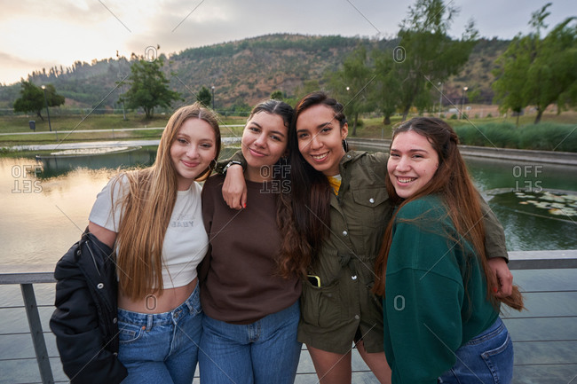 A group of beautiful young women posing near a lake in a park on a sum