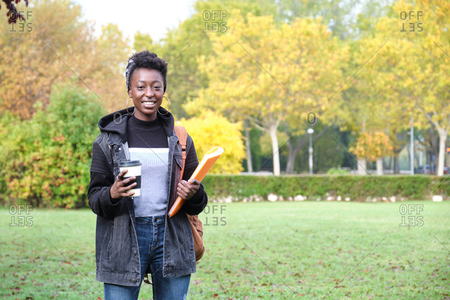 University female african student with backpack, folder and a cup of coffee outside on campus. College life concept.