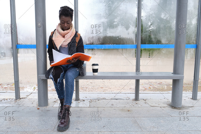 University female african student studying her lecture notes while is waiting for a bus on campus. College life concept.