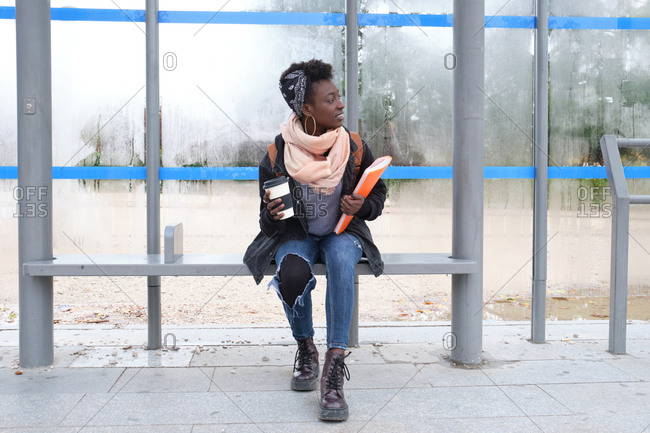 University female african student waiting for a bus holding a coffee cup and a folder on campus. College life concept.